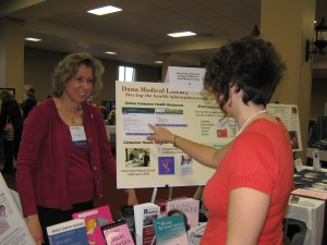 Nancy Bianchi, MLS, with attendee at Dana exhibit table.